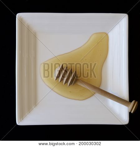 Honey with a wooden dipper on a white plate.