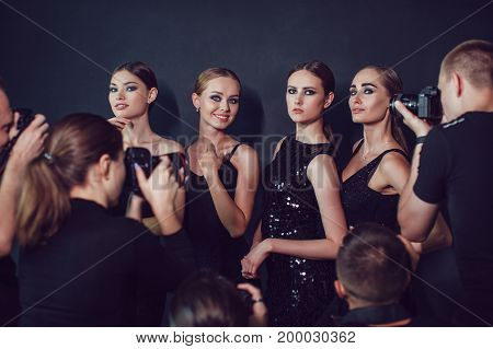 Photographers paparazzi take photos of women in cocktail dresses on dark background.