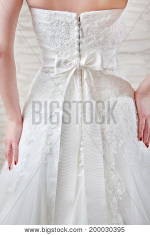 View of the back, with a beautiful white bow at the waist.