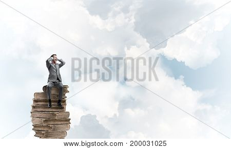 Frustrated businessman sitting on books and closing ears with hands