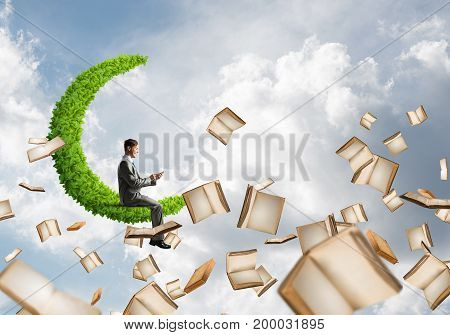Young businessman floating on green moon in blue sky with smartphone in hands