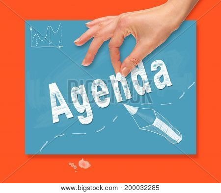 A Hand Picking Up A Agenda Concept On A Colorful Drawing Board.