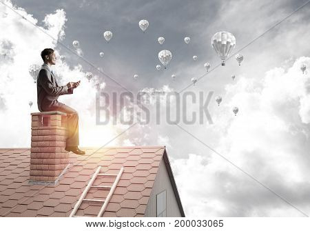 Young businessman sitting on house with smartphone in hands