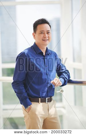 Portrait of cheerful Singaporean businessman standing at window