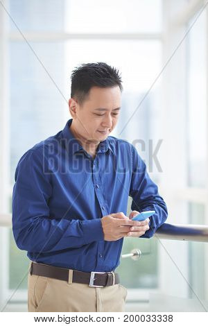 Portrait of texting Singaporean business executive standing at window