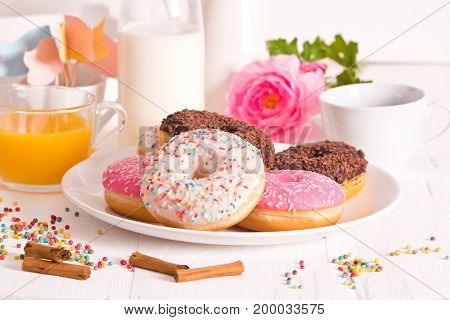 American donuts with rainbow sprinkles on white dish.