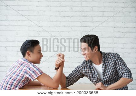 Cheerful teenage boy wrestling with his father