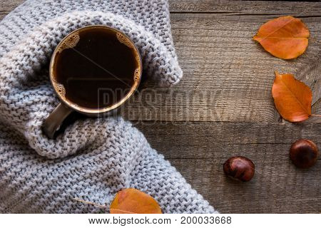 Cup of coffee wrapped in warm scarf on wooden board. Top view vintage style Still life. Flat lay.