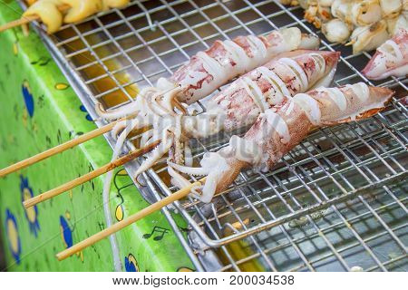 Grilled squid placed on a stainless steel sieve.