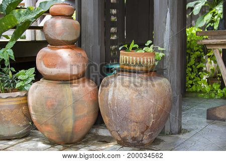 Old orange earthen jars stacked next to a wooden pole.
