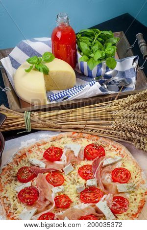 Home made raw pizza with prosciutto and blue cheese. The dough with the addition of fiber and Provencal herbs