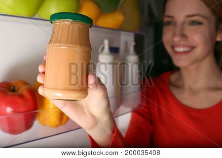 Young girl taking jar with sauce from fridge