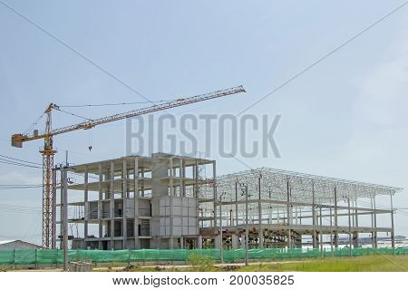 Crane lift with factory under construction on day ligth