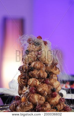 Sweet cake decorated with sugar cobwebs and berries. Lamp and blue background.