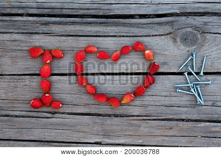 Text I love nails made from strawberry on wooden background. Concept of home repairs