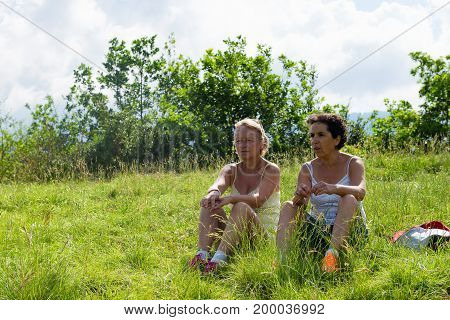 Two mature women resting and sitting in the grass