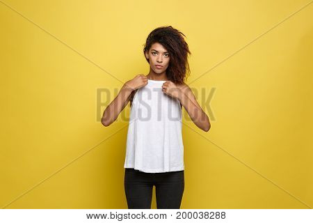 Beautiful attractive African American woman posting and dressed up her white t-shirt. Yellow studio background. Copy Space.