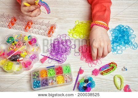 rubber, craft and fashion concept - colored elastics and devices for weaving of rubber band bracelet on wooden background