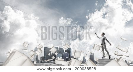Man in casual wear keeping hand with book up while standing among flying books with cloudly sky on background. Mixed media.
