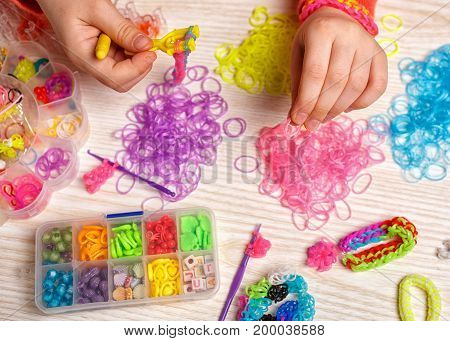 handwork, weaving rubber and effort concept - hands weaving of colored rubber band bracelet, closeup, wooden background