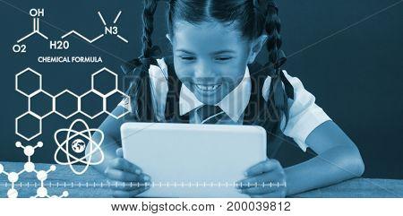 Graphic image of chemical formulas against schoolgirl using digital tablet against blackboard