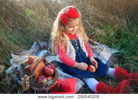 Little girl on nature with a basket of fruit and books.