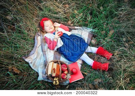 Little girl lying in grass on a plaid with a basket of fruit in the autumn day.
