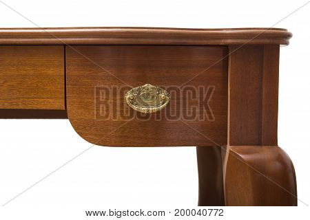 Part of an antique wooden handcrafted table with gold metal handle and a shelf on isolated white background