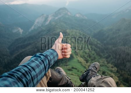 Traveler young man sitting in summer mountains and showing thumb up gesture point of view shot.