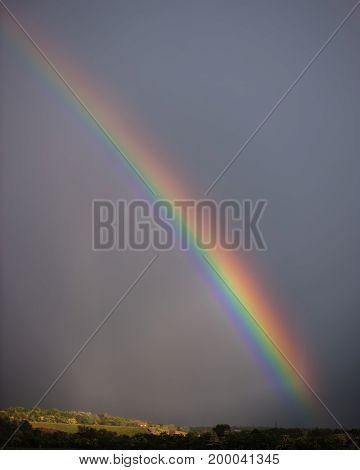 Rainbow against a background of a dark rain sky in the countryside