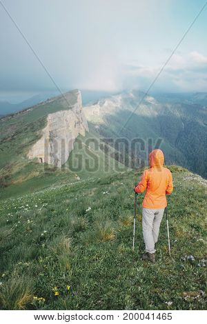 Hiker young woman with trekking poles walking on mountain ridge in summer rear view.