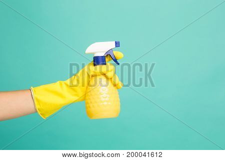 Close up picture of afemale hand and house-cleaning spray on a blue abstract background