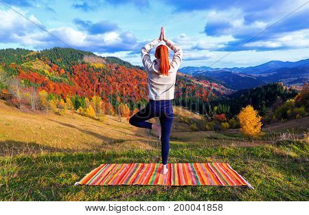 The yogini stands on a striped mat and meditates among beautiful mountain landscapes on an autumn day.