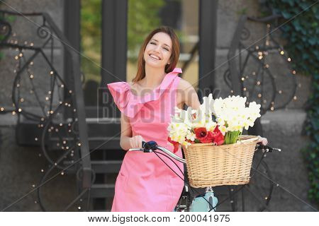 Young beautiful girl and bicycle with basket of flowers on city street
