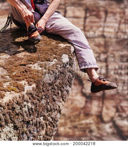 Unrecognizable young man sitting on edge of cliff and putting on climbing shoes.