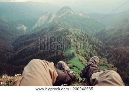 Hiker young man sitting over mountain ridge in summer point of view.