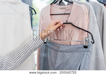 Cropped Shot Of Woman Choosing Clothes In Showroom