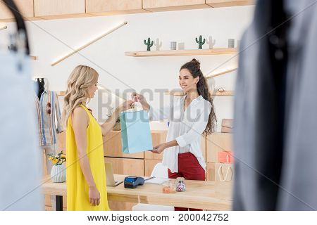Cashier Giving Shooping Bag To Beautiful Female Customer In Clothes Store