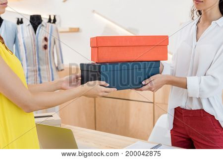 cropped shot of cashier giving shoe boxes to woman