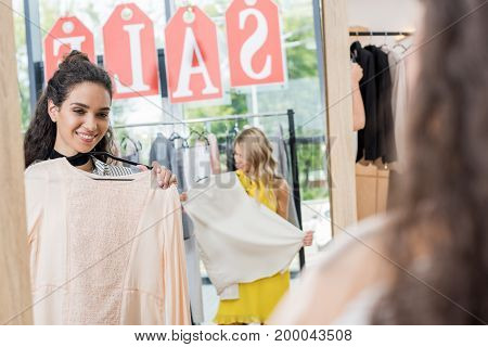 view of young happy women in clothes store