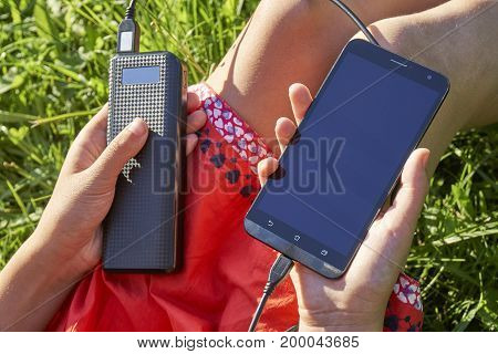 Young girl charging her smart phone with power bank sitting on green grass outdoors