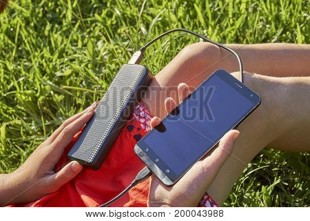 Girl holding powerbank connected with mobile phone sitting on green grass outdoors
