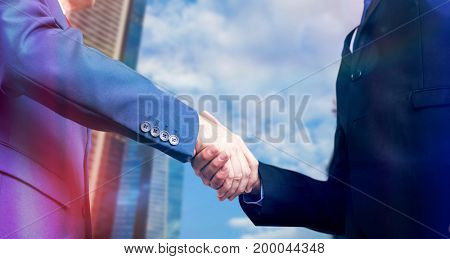 Businessman shaking hands against city