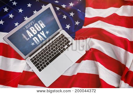 Blurry animated flare against laptop on american flag with fourth july theme