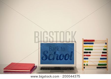 Back to school text over white background against books with laptop and abacus on table
