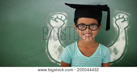 Portrait of cheerful girl wearing eyeglasses and mortarboard against green chalkboard