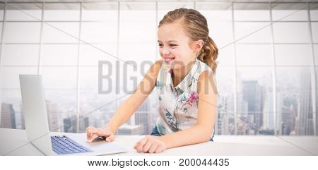 Girl using laptop at table against modern room overlooking city