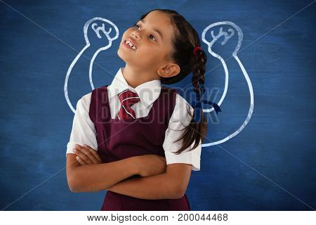 Thoughtful schoolgirl looking away against blue background