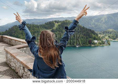 the girl looks at the mountain views. valley view and lake on Alps the background. Travel Slovenia, Europe. Bled Lake with Island, Castle and Alps Mountain on background.