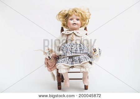 Portrait of a ceramic porcelain handmade vintage doll with big blue eyes and opened mouth with curly blond hair in a knitted old plaid dress sitting on a wooden chair on white background.